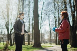 two people conversing while practicing social distancing